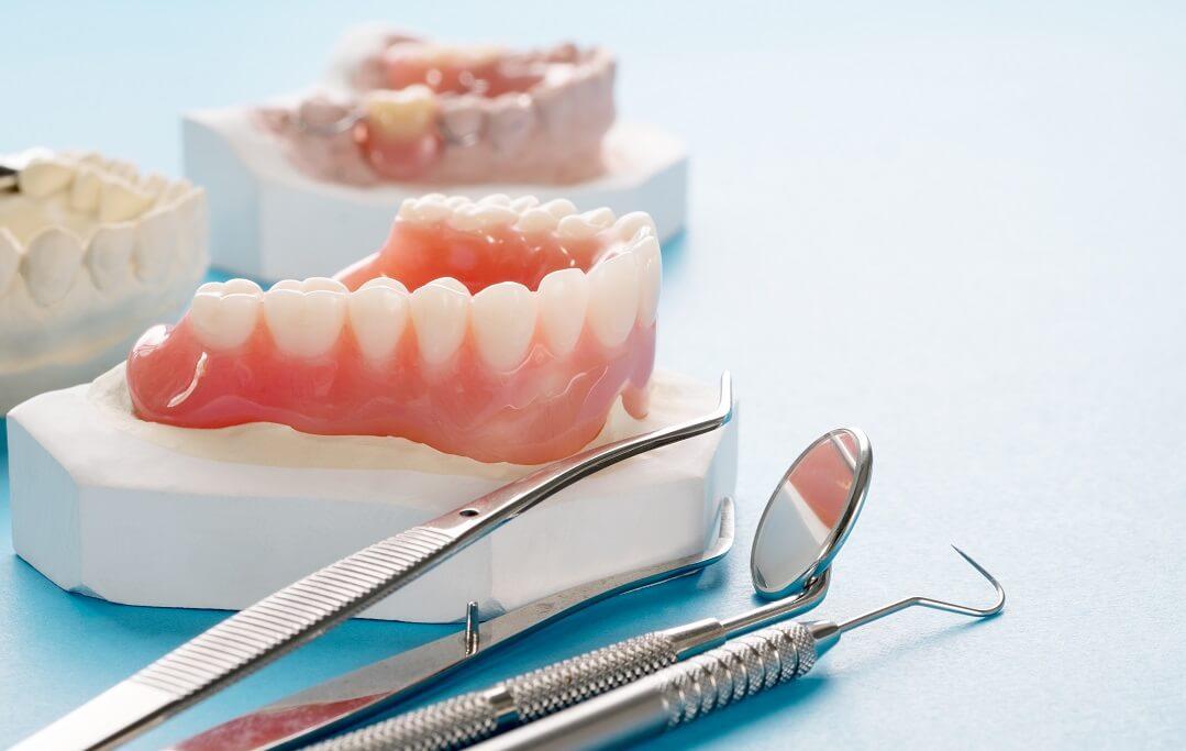 Različite vrste proteza i zubarski pribor na svijetloj površini