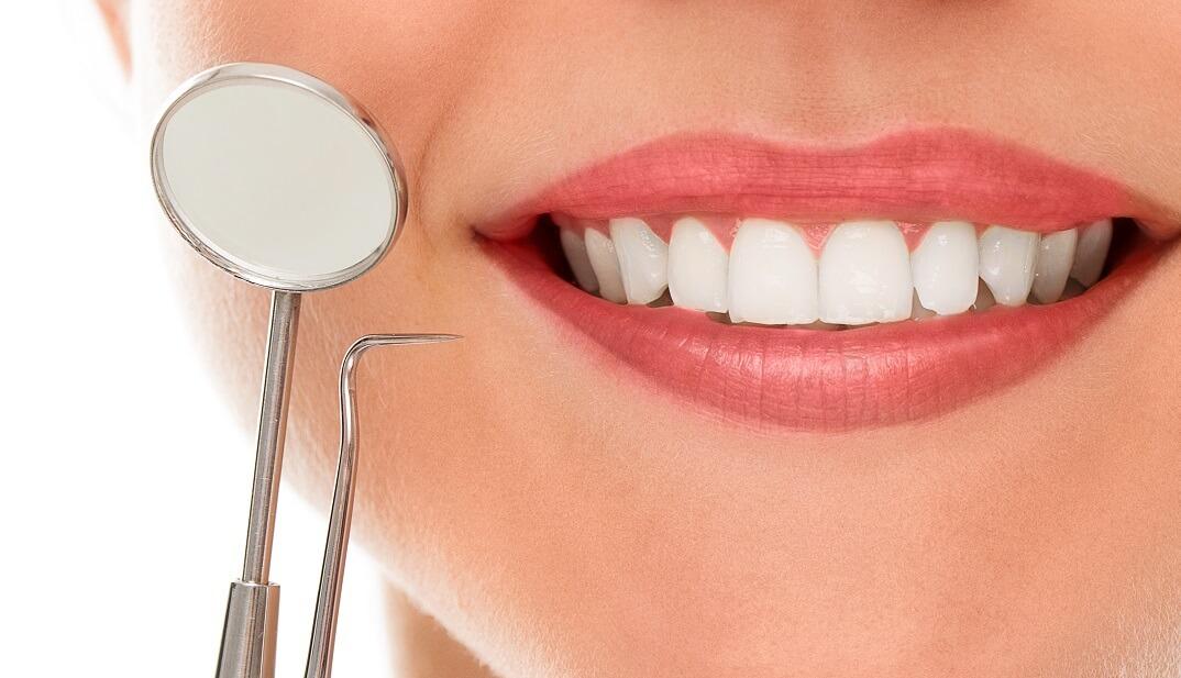 Ženska osoba sa zdravim bijelim zubima se smiješi i drži stomatološki pribor kraj usta